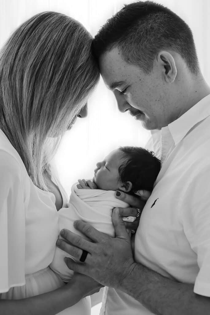 black and white studio family photograph with newborn
